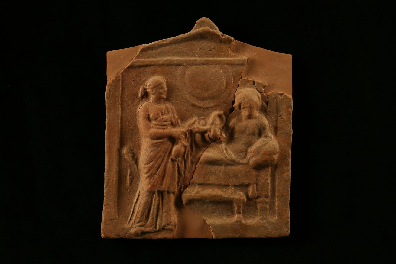 Votive plaque from inside the tomb featuring relief depiction of funerary banquet. Related to rituals of ancestor or hero worship.  Antheia. Tholos tomb. 4th c. B.C.